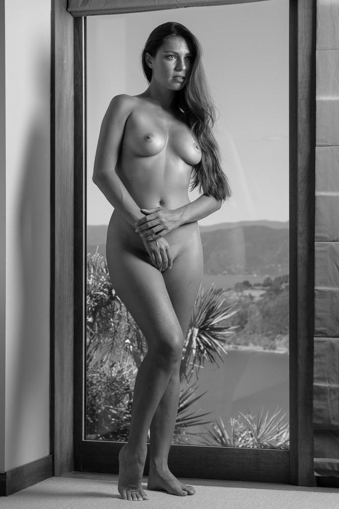 Art nude woman standing contrapposto in window with view of Miramar Peninsula, Wellington, New Zealand NSFW