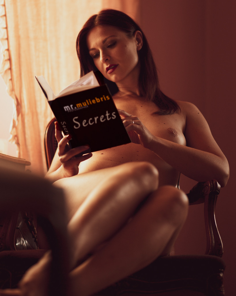 Topless woman reading book by orange curtain in natural light NSFW art