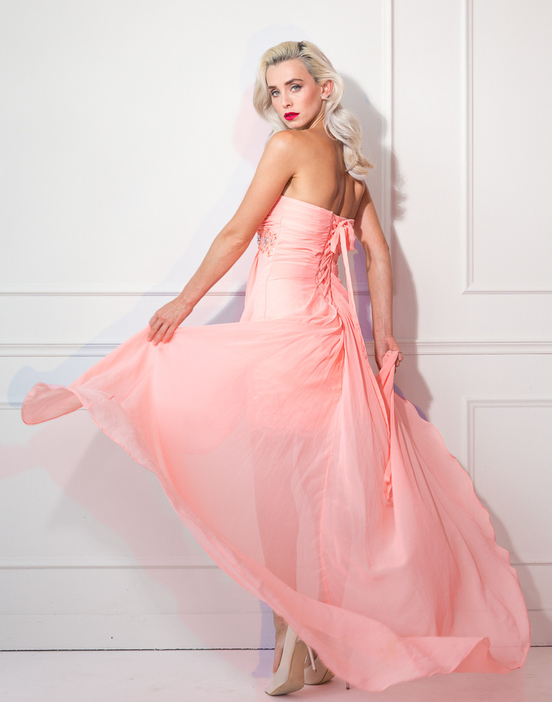 Fashion image of woman swirling salmon pink evening gown