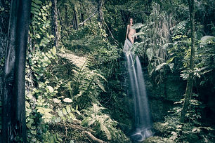 woman posing nude above a waterfall in New Zealand native forest