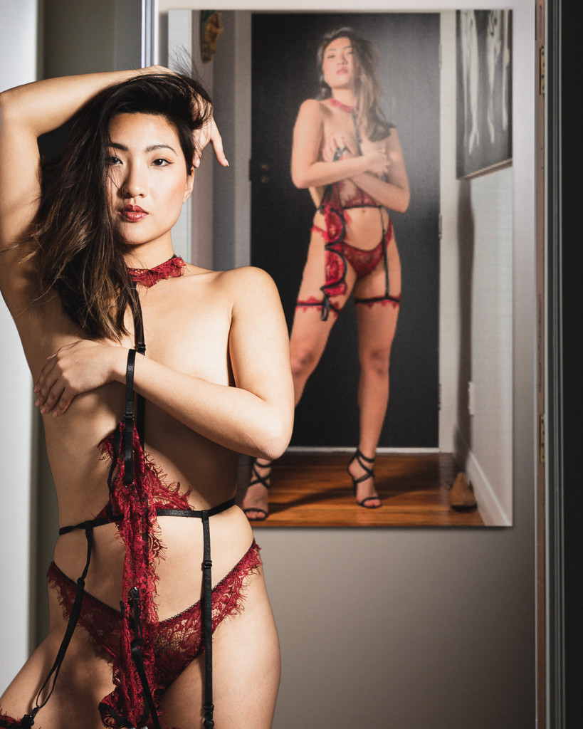 Beautiful Asian woman in red lingerie covering herself with hands with surreal painting of herself on wall in composite NSFW art work