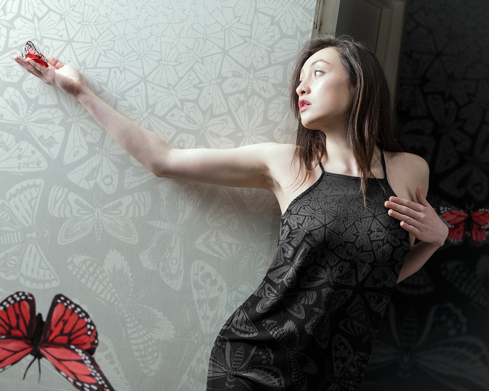 Woman wearing dress with butterfly tessellations holding red Monarch butterfly by butterfly wallpaper
