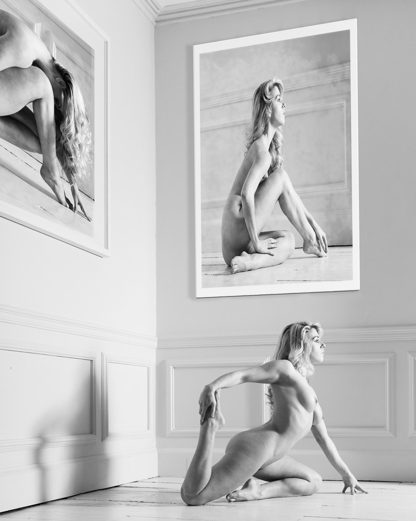 Monochrome fine art nude of woman in elegant pose on floor with images of herself on walls NSFW