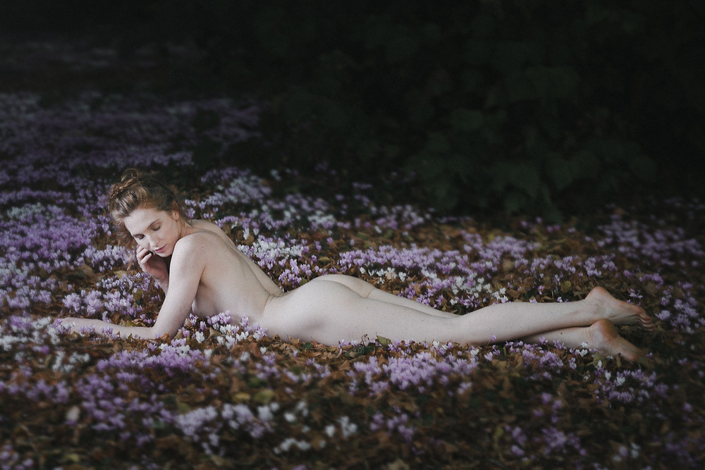 Beautiful pale nude ginger haired woman reclining in autumn garden with pink and purple flowers
