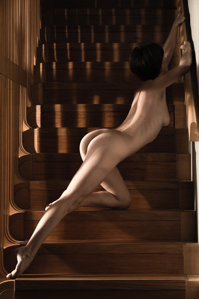Classical nude study of elegant woman posed diagonally across curved wooden staircase