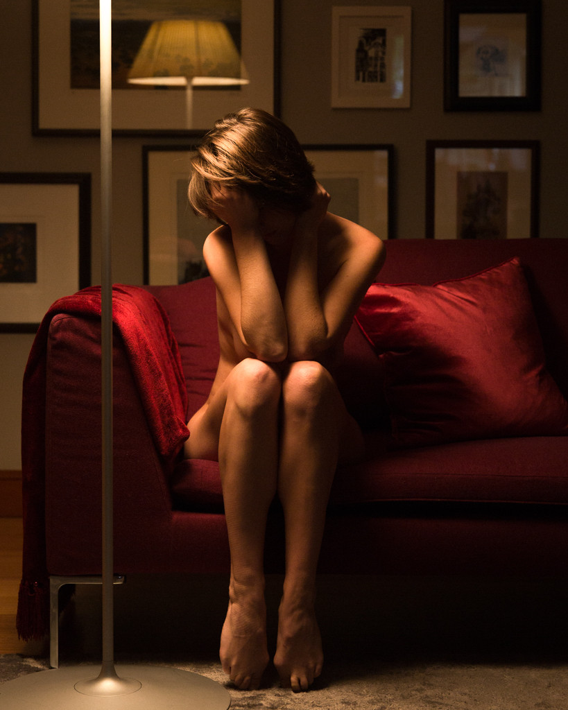 Sad woman with face averted on red sofa dramatically in NSFW artlit by lamp
