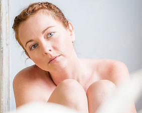 Portrait of a pale beautiful ginger haired blue eyed young woman with knees to chin looking at camera