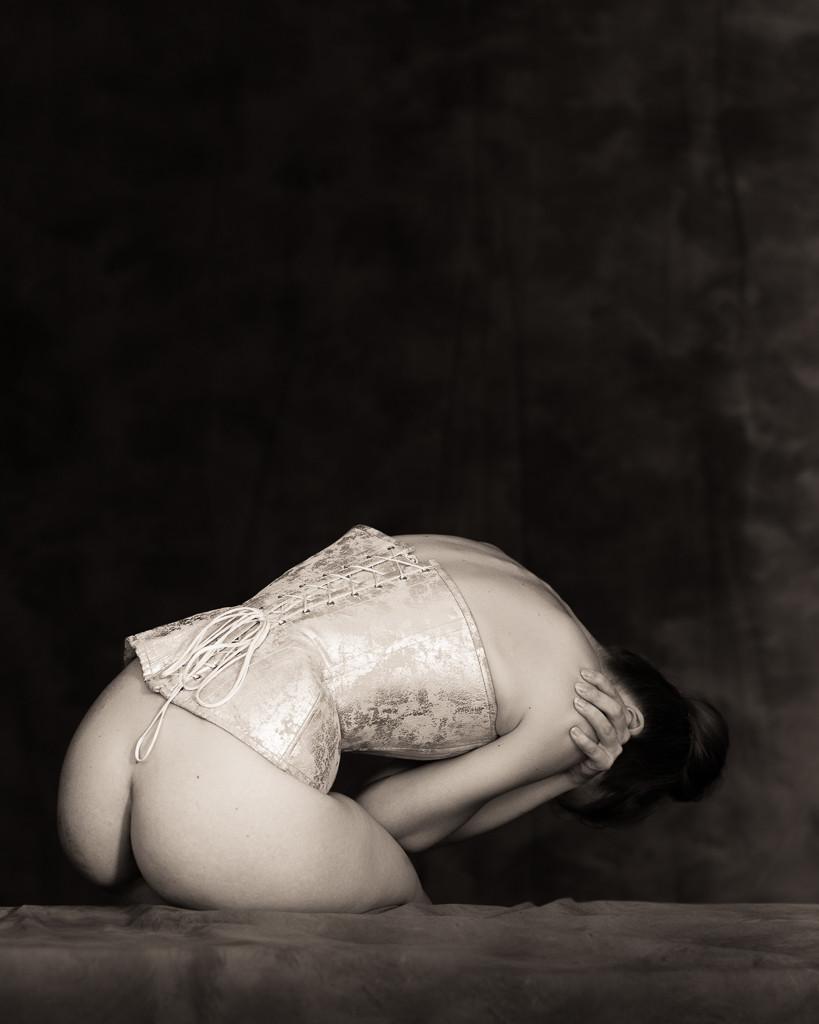 Classic monochrome woman in beautiful corset bent in despair