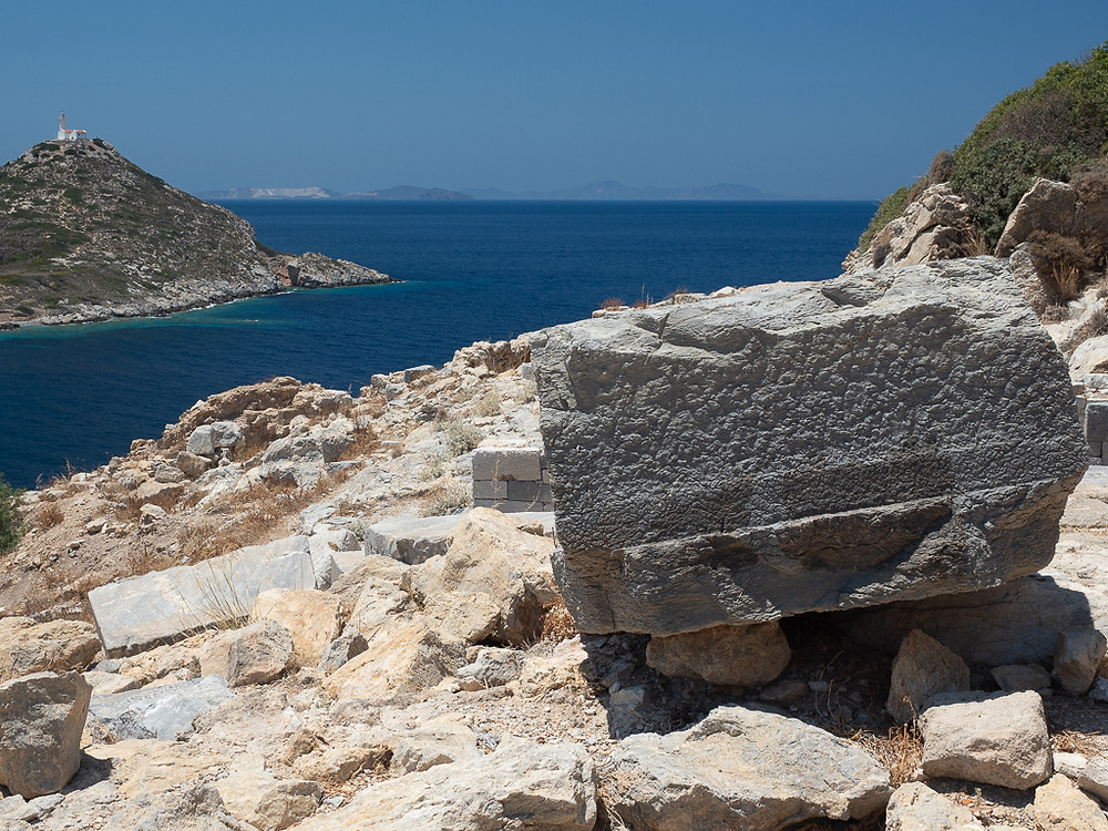 Knidos ruins view West with blue wine dark sea and large temple boulder