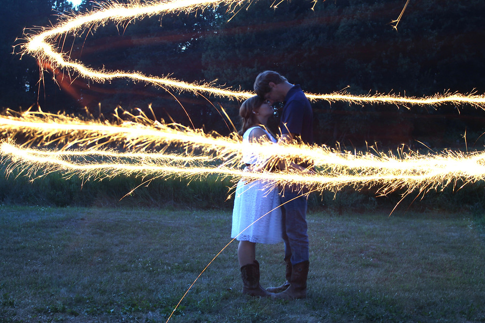 couple hugging in filed with sparkles circling them