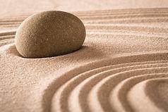 Stein und Sand mit eingearbeiteten mustern im Sand. Eine Meditive übung zur einstimmung für die ausbildung zum schamanen