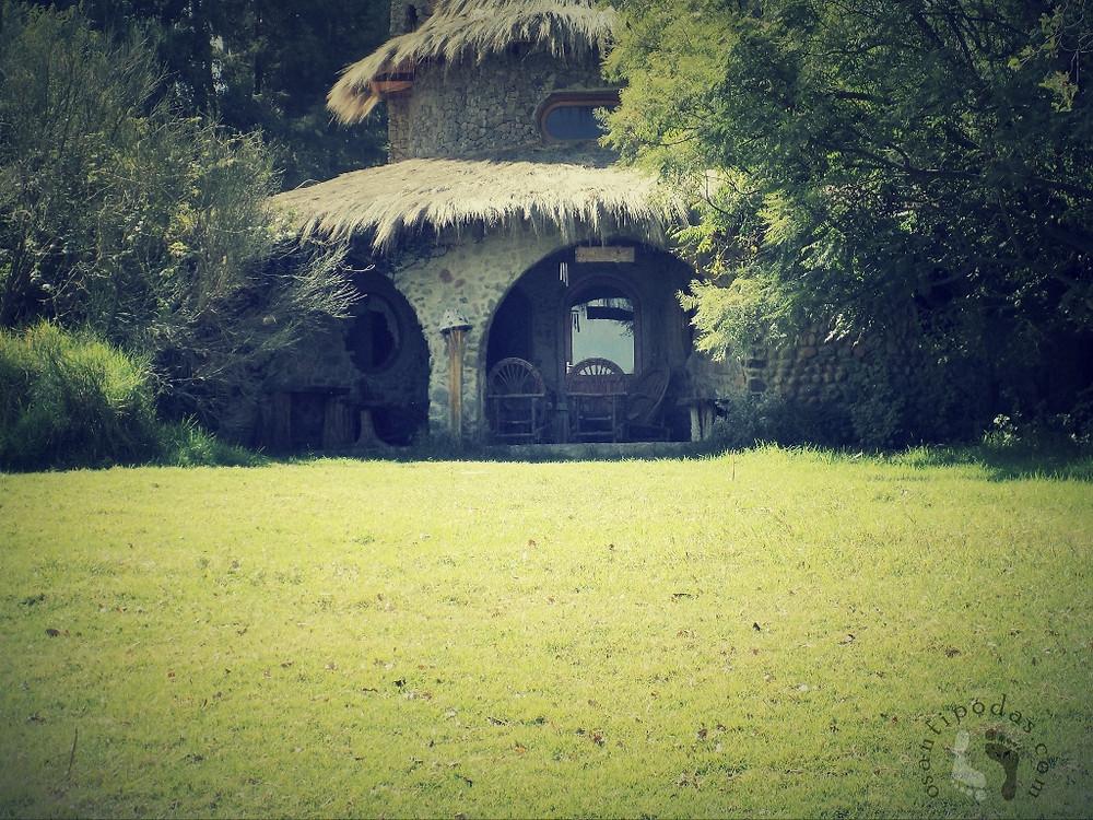 Casa de pedra com teto de palha, e um gramado verde adiante