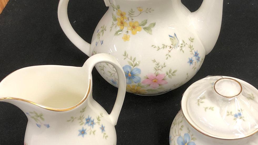Tea pot with cream and sugar.
