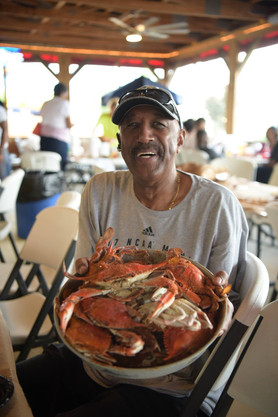 smiling man holding tray or Crab Place c