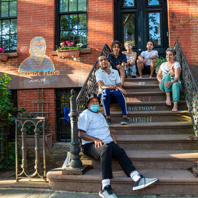 Laurence and Reggie with their kids, Simon, Emanuel & Esther, and grandma Sheila. Simon chalked the George Floyd mural in front of their Boerum Hill home