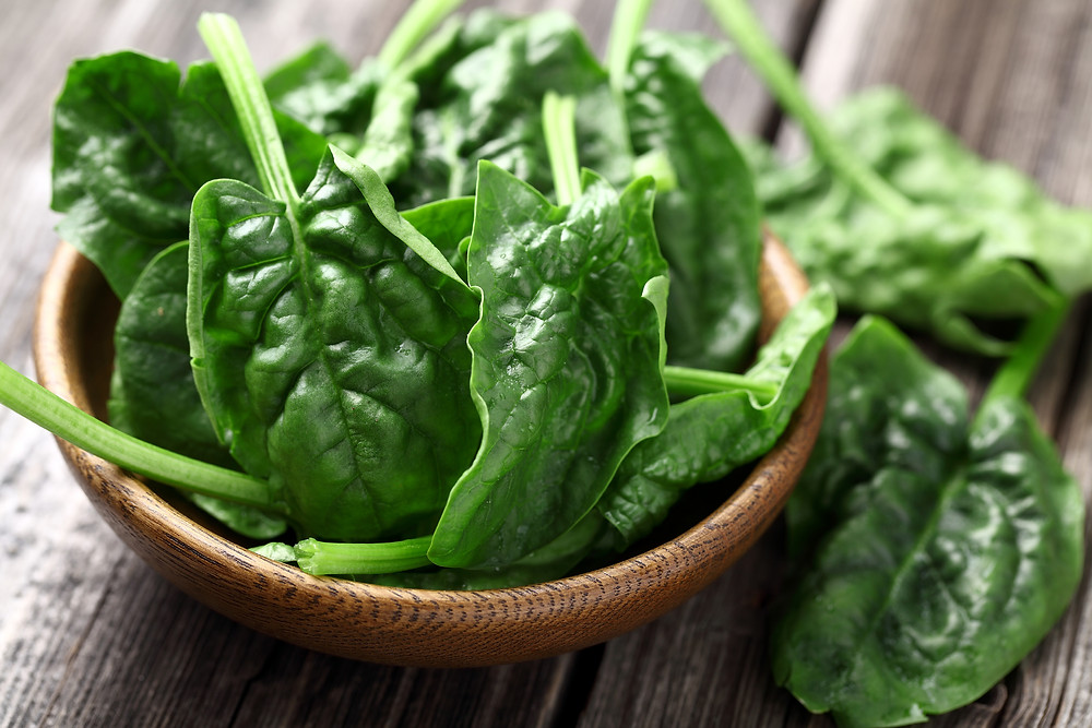 Spinach leaves in a wooden plate.jpg