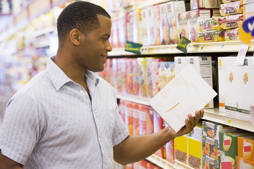 Man Reading Packet In Supermarket.jpg