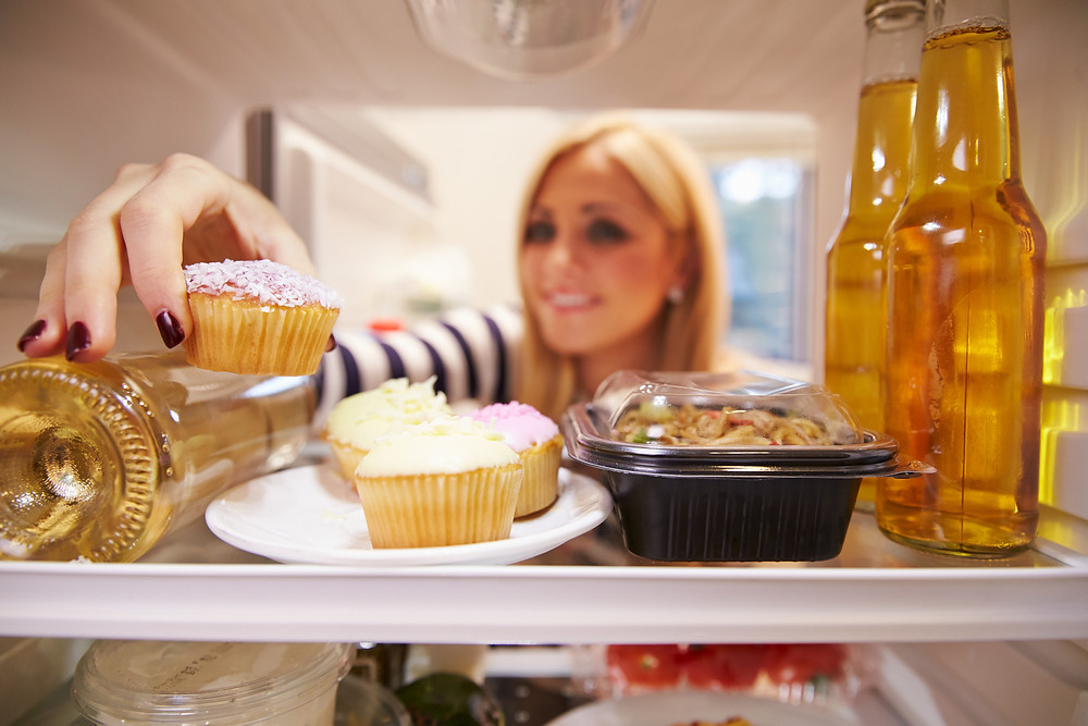 Woman Looking Inside Fridge Full Of Unhealthy Food.jpg