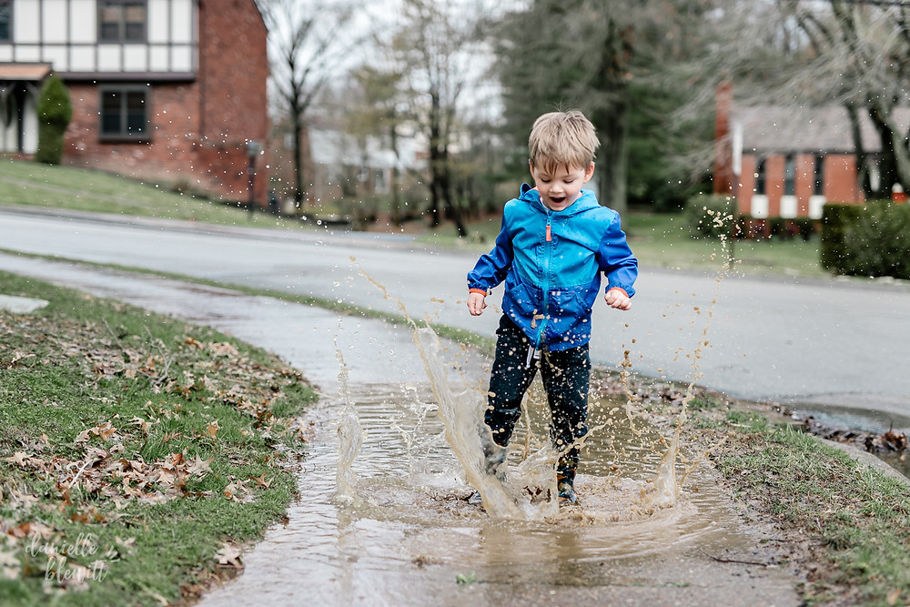 little boy jumping in a muddle puddle