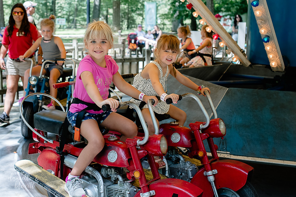 two little girls riding the rides at idlewild amusement park