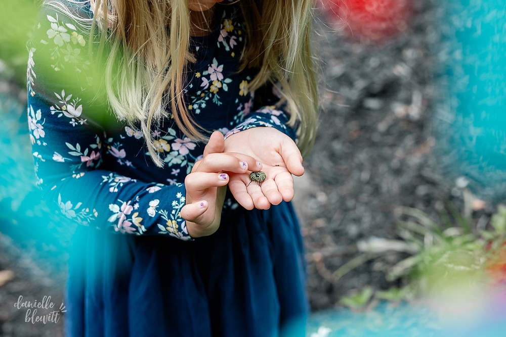 photo of little girl holding a catepillar