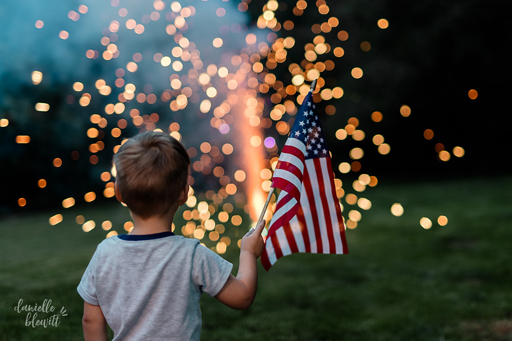 little boy holding an american flag watching fireworks