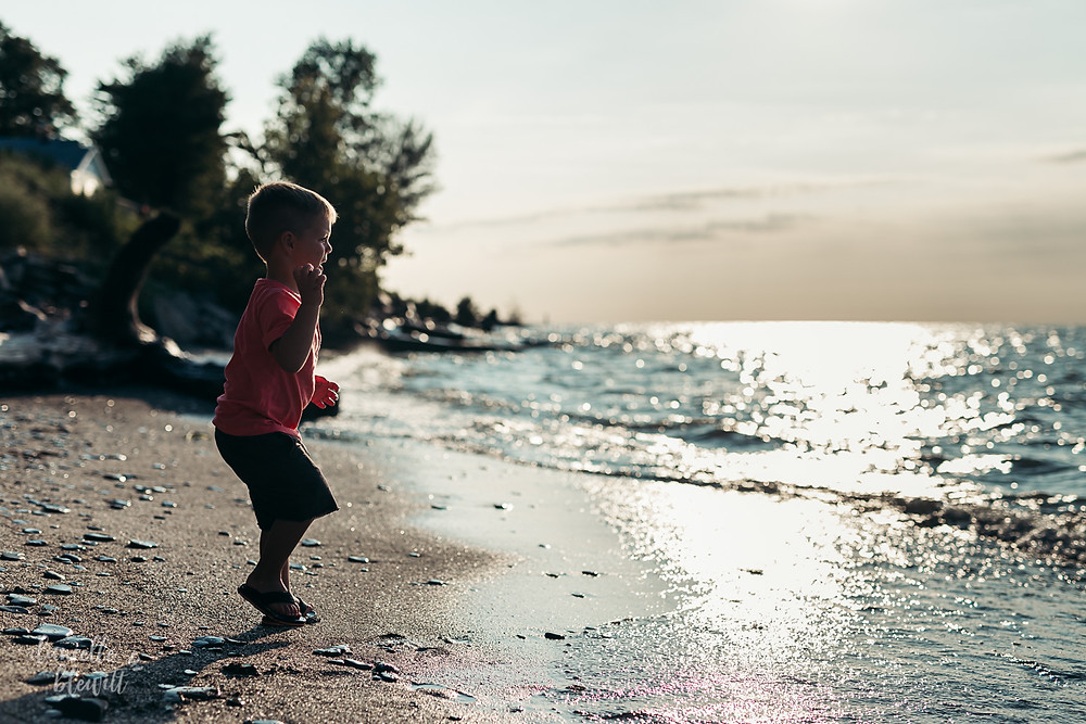 little boy on a beach at sunset
