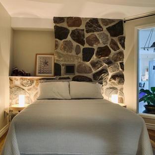 Une superbe chambre des maîtres avec mur de pierre