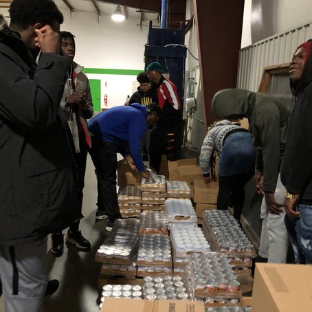 YouthBuild Students Pack Food to Help Children in Need