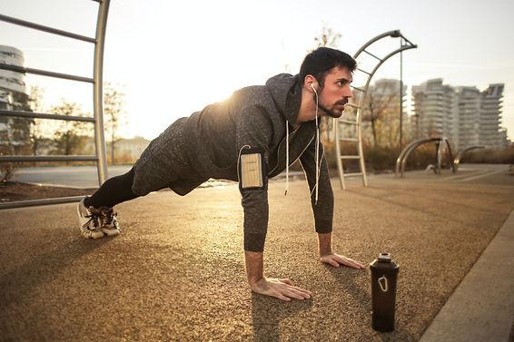 man-in-gray-jacket-doing-push-ups-during