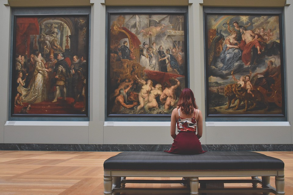 Woman enjoying paintings at the Louvre museum