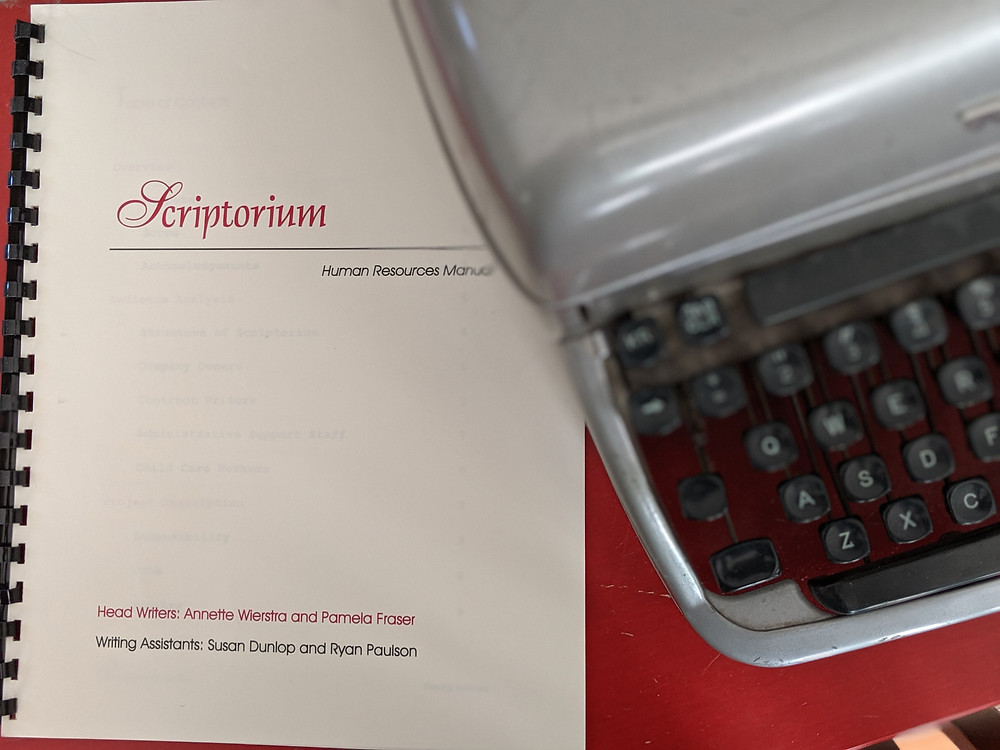 Our original assignment. We've kept it all these years to fondly remember when we first decided to start our company. A photo of a cerlox bound document next to a typewriter