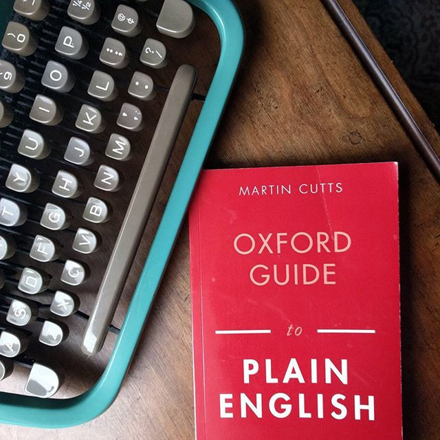 Typewriter next to the book Oxford Guide to Plain English by Martin Cutts.