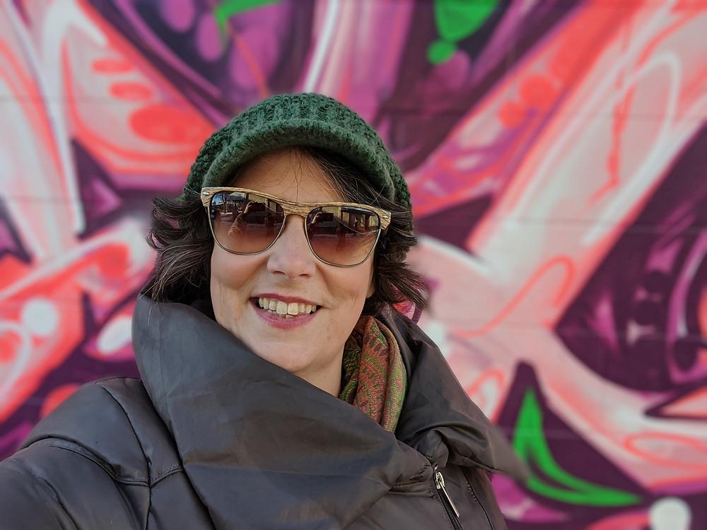 Annette in winter gear in front of an instagrammable wall in Edmonton's Chinatown.