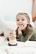 photo-of-a-happy-kid-lying-on-white-bed-