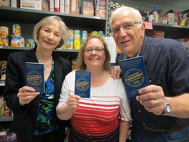 three people holding up passport to savings passports