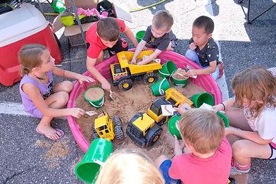 Kids playing with toy trucks in sandbox