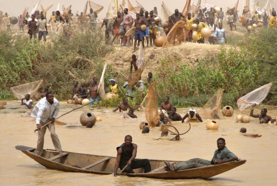 fishermen-racing-into-the-water-in-argungu