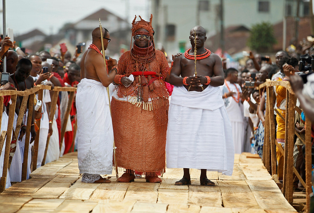 Newly crowned Oba of Benin Kingdom Eheneden Erediauwa is guided through a symbolic bridge by the palace chiefs during his coronation in Benin city