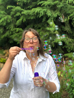 sarah blowing bubbles in a garden