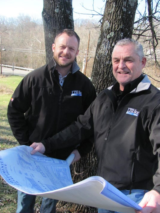 Scott Lucke and Bob Lucke holding custom home floor plan drawings on site in Mason, Ohio