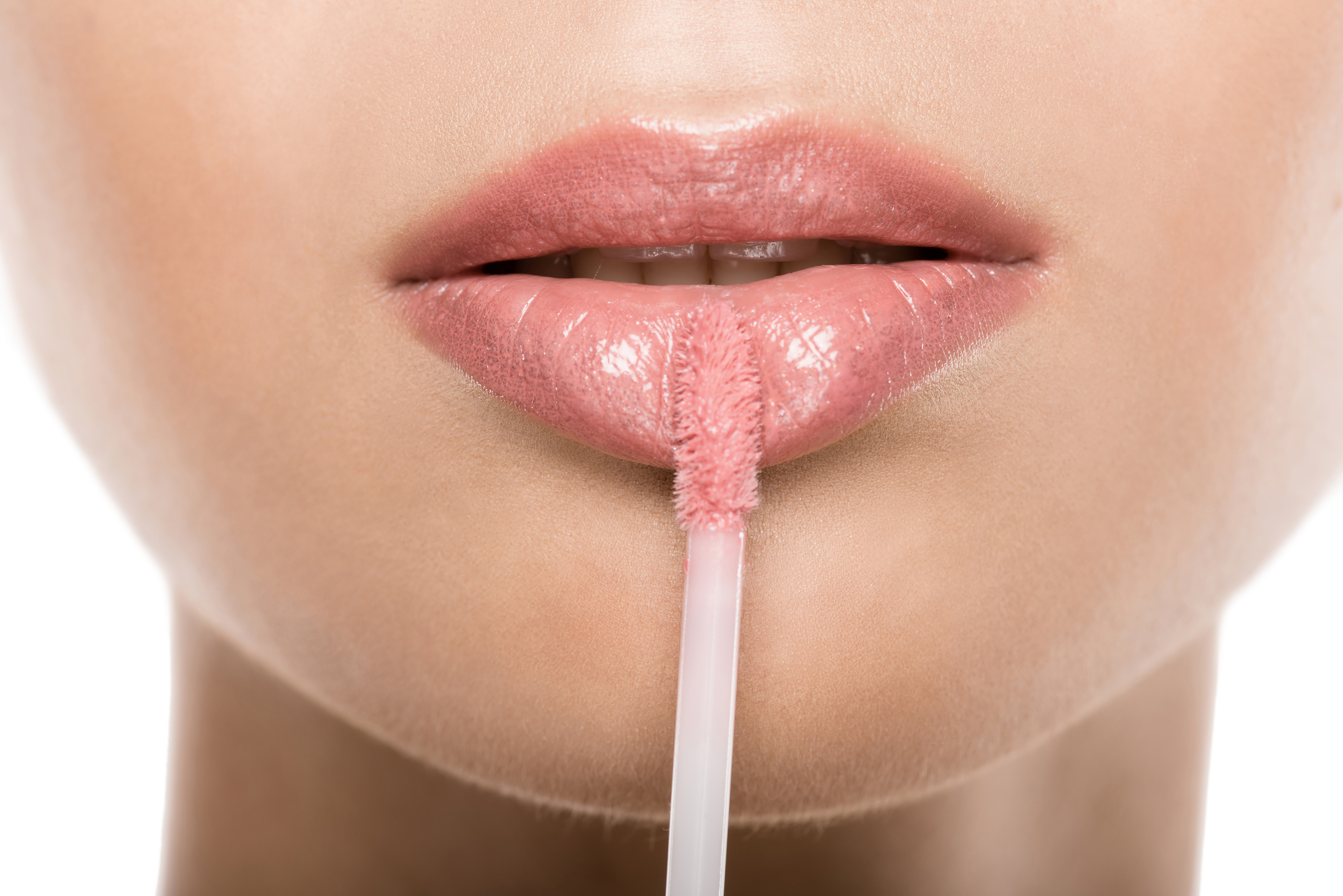 Close Up View Of Beautiful Woman Applying Pink Lipgloss On Lips, Isolated On White