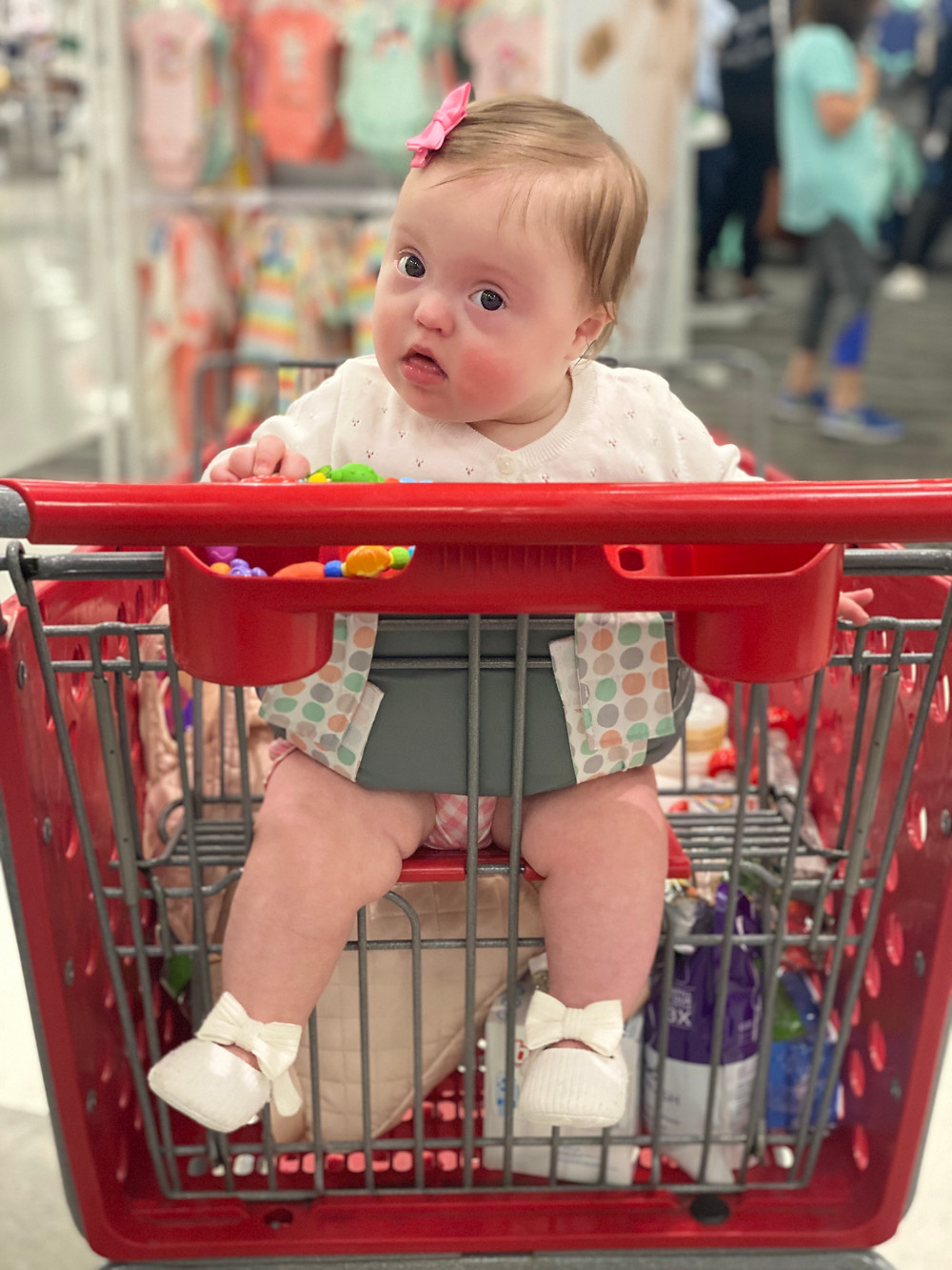 Adeline sitting in a shopping cart with the help of The Swing Thing