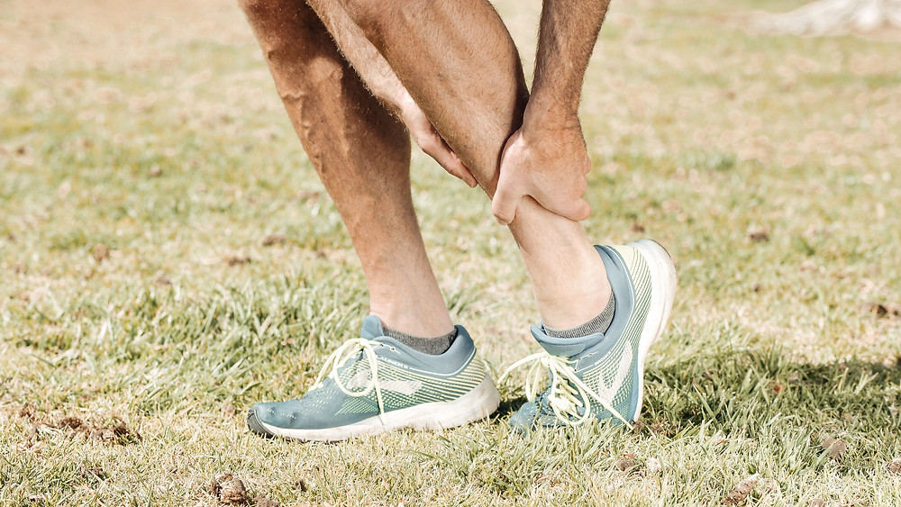 Man grabbing ankle in relation to foot orthoses that could help prevent injury