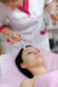 professional-woman-applying-green-cream-