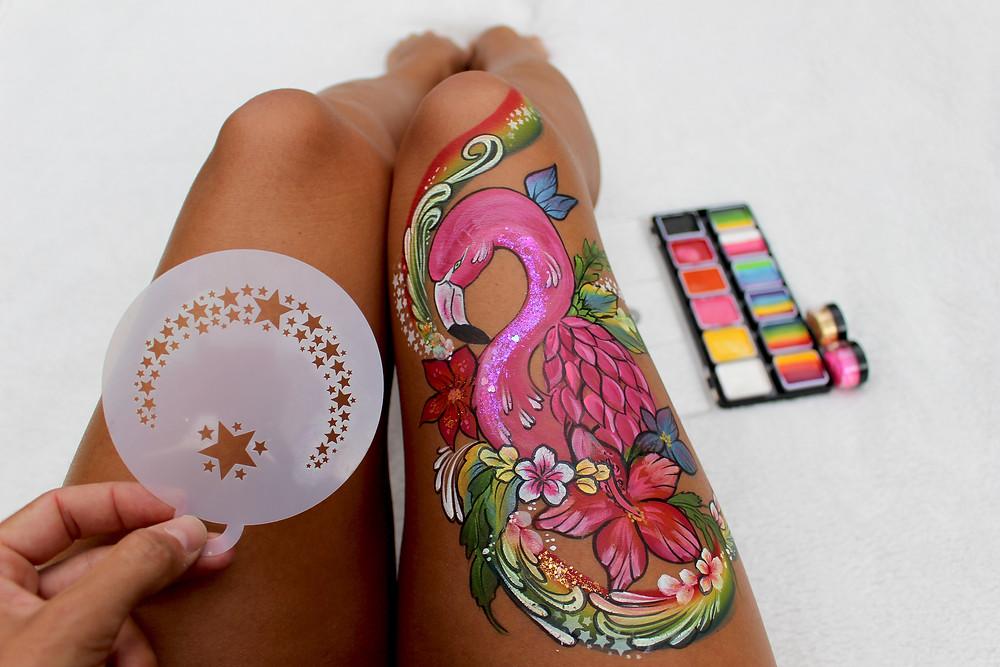 flamand rose peint sur une cuisse et pochoirs et paillettes