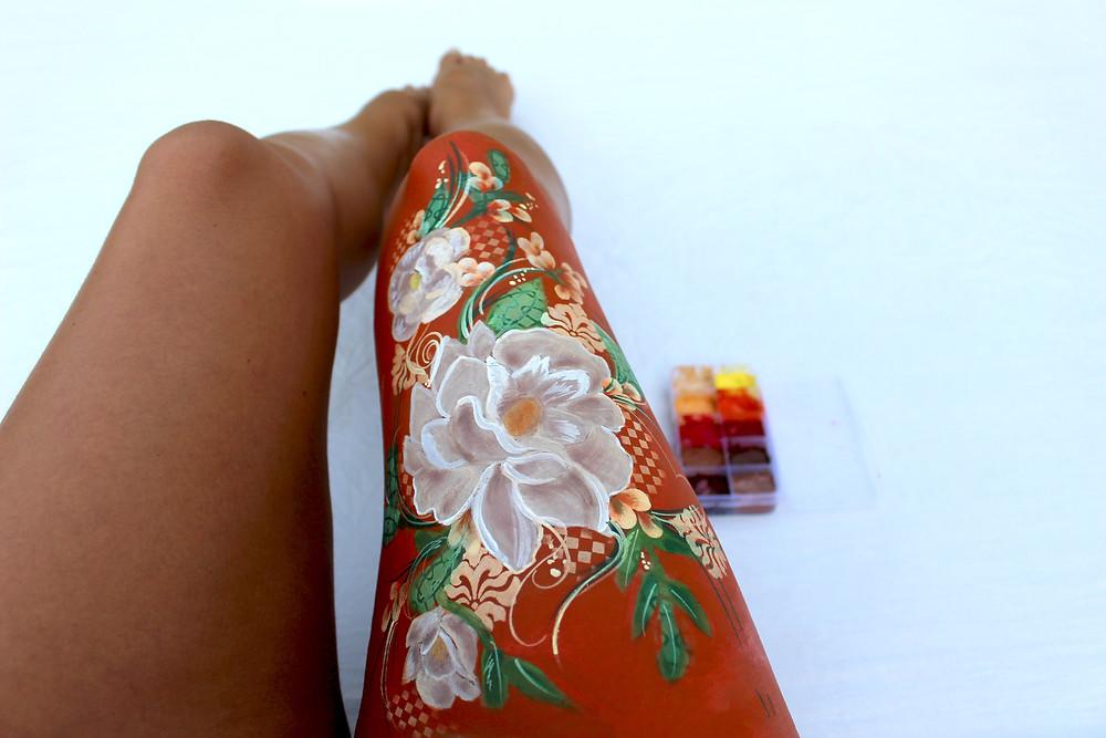 jambe peinte, fleurs orangées et feuillage, bodypainting