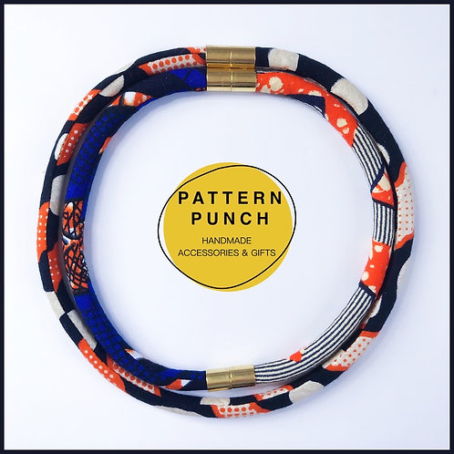 Lightweight fabric rope necklace set in African wax print fabric with magnetic clasp in black & orange. Pattern Punch