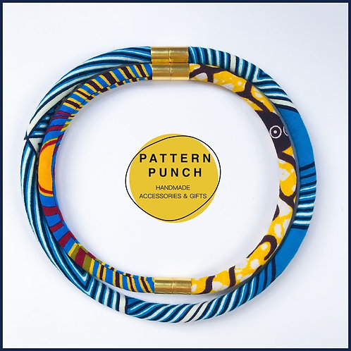 Lightweight fabric rope necklace with magnetic clasp in blue, white and yellow African print fabrics.