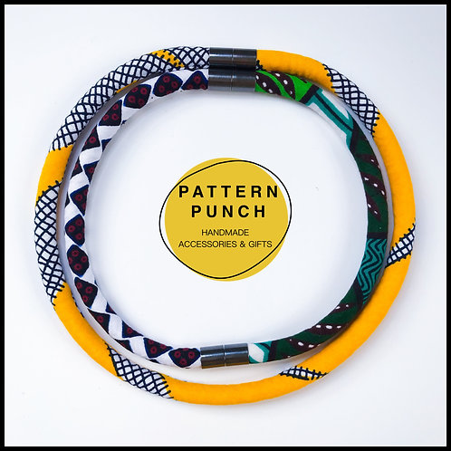 Lightweight fabric rope necklace with magnetic clasp in white, green and yellow African print fabrics.